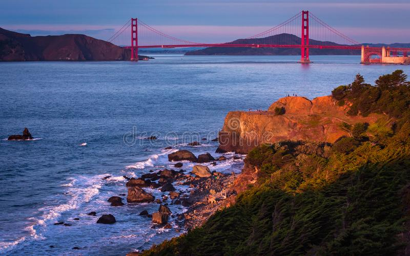 Golden gate bridge et coucher du soleil sur les roches photo stock