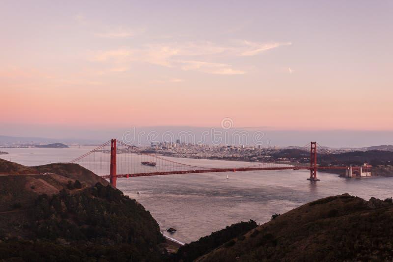 Golden gate bridge i rosa glöd av skymningberg, horisont arkivfoton
