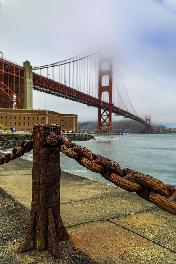 Golden Gate bridge with low fog rolling in San Francisco, California. The famous Golden Gate bridge on a cloudy summer day with low hanging fog rolling in San stock photography