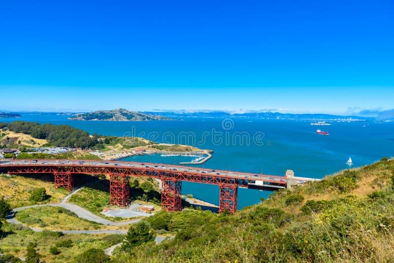 Golden gate bridge mit den Skylinen von San Francisco im Hintergrund an einem schönen sonnigen Tag mit blauem Himmel und Wolken i lizenzfreie stockbilder