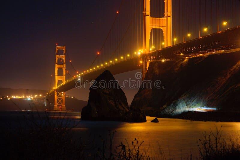 Golden Gate Bridge. Night bridge San Francisco Bay with rocks water long exposure raw royalty free stock images