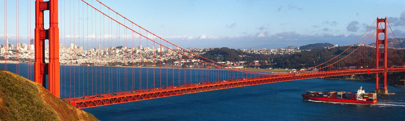 Golden gate bridge och ett behållareskepp arkivbild