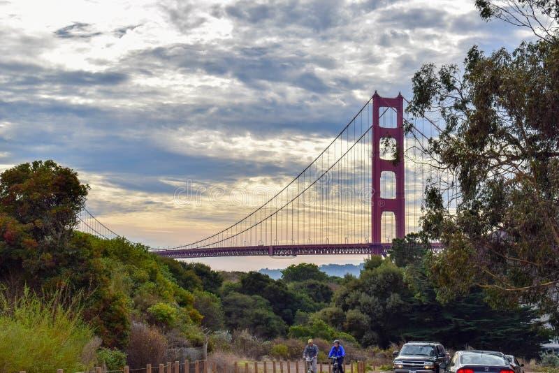 Golden gate bridge-Sonnenuntergang und -radfahrer auf Marin County Road stockbilder