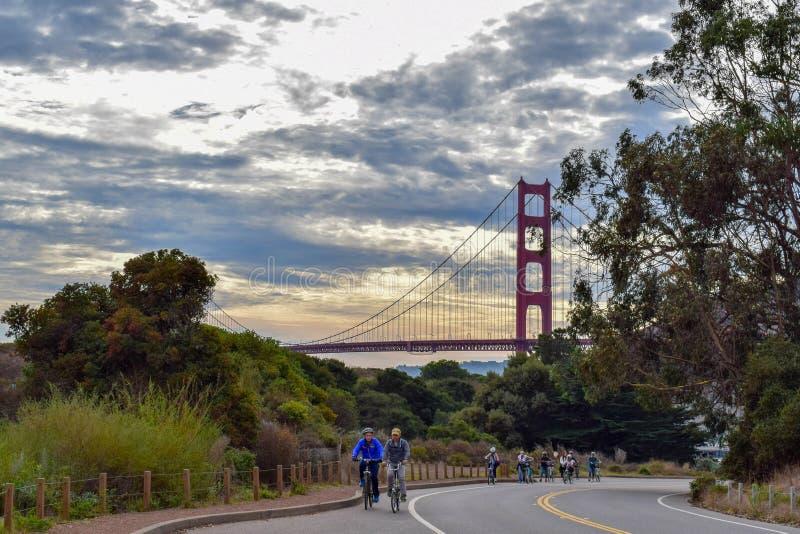 Golden gate bridge-Sonnenuntergang und -radfahrer auf Marin County Road stockfotografie
