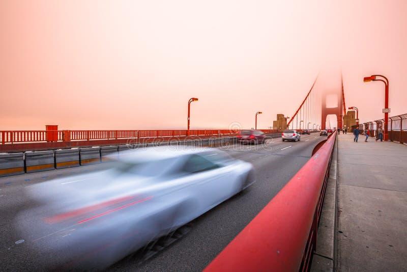 Golden gate bridge-Sonnenuntergangautos stockbilder