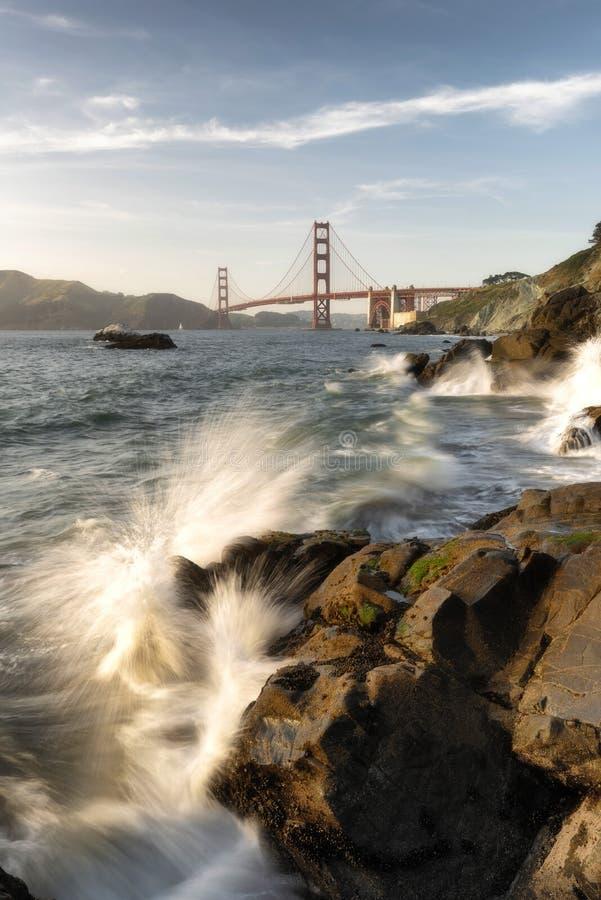 Golden gate bridge van Baker Beach met golven die op rotsen, San Francisco, Californië verpletteren stock foto