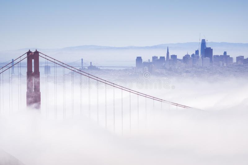 Golden Gate and the San Francisco bay covered by fog, the financial district skyline in the background, the Salesforce tower. Almost finished, as seen from the stock photo