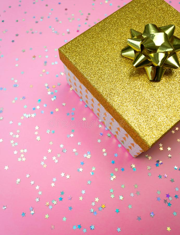 Golden gift box and rainbow holographic stars confetti on led neon pink background. Trendy magenta holiday vertical concept. Golden gift box with ribbon and stock images