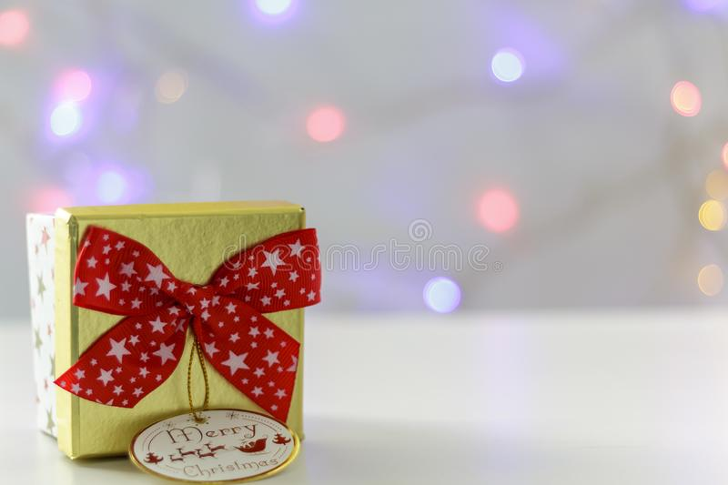 Golden Gift box with red bow and defocused christmas lights on the background stock image