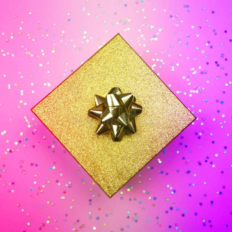 Golden gift box with ribbon and rainbow holographic stars confetti. Top view square banner, social media. Golden gift box with ribbon and rainbow holographic royalty free stock images