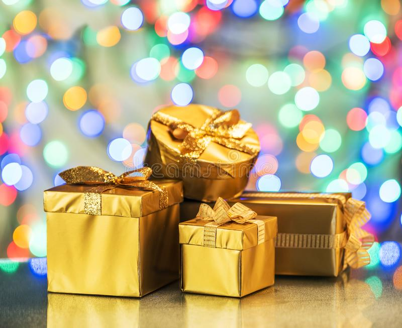 Golden gift boxes as a symbol of wishes and celebration. Colorful blurred bokeh background stock photo