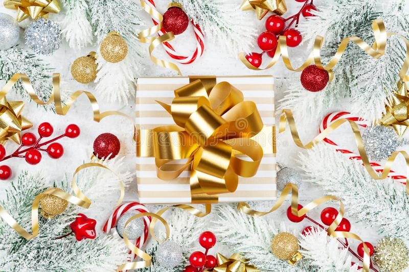 Golden gift or present box, snowy fir tree and christmas decorations on white wooden table top view. Flat lay. royalty free stock photography