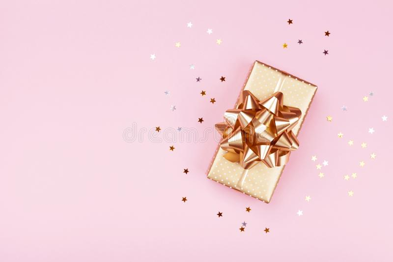 Golden gift or present box and stars confetti on pink table top view. Flat lay composition for birthday, christmas or wedding. royalty free stock photo