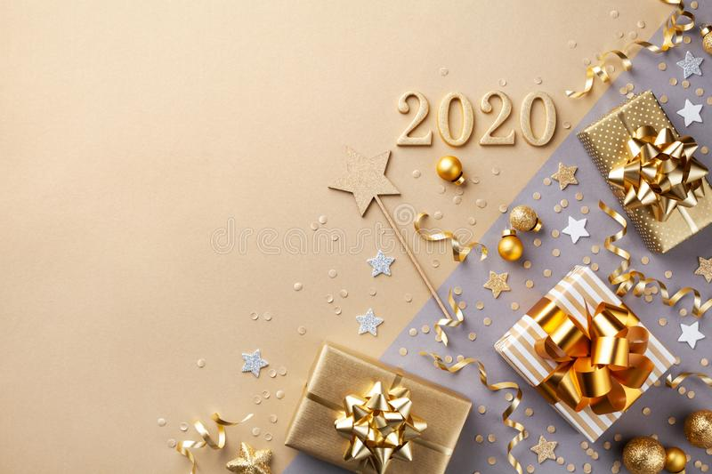 Golden gift or present boxes with golden bows, 2020 number and confetti top view. Christmas and New Year background. Flat lay stock photography