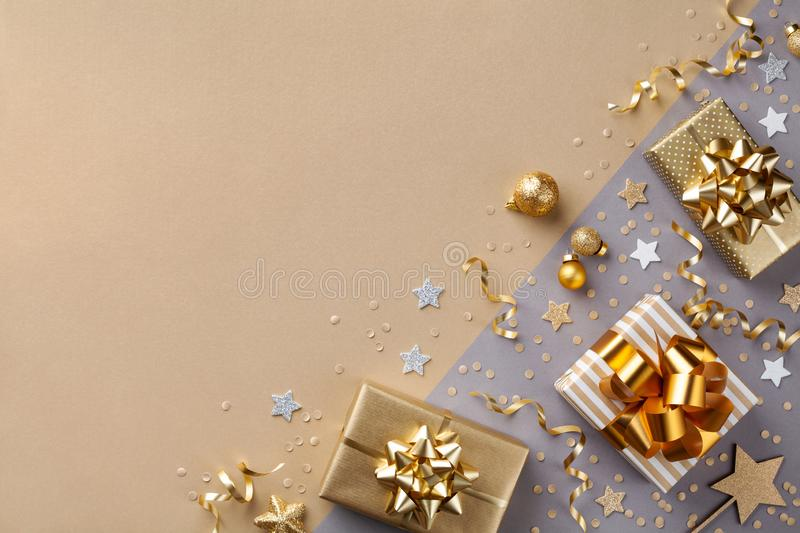 Golden gift or present boxes with golden bows and star confetti on bicolor background top view. Flat lay composition for Christmas. Greeting card stock photography