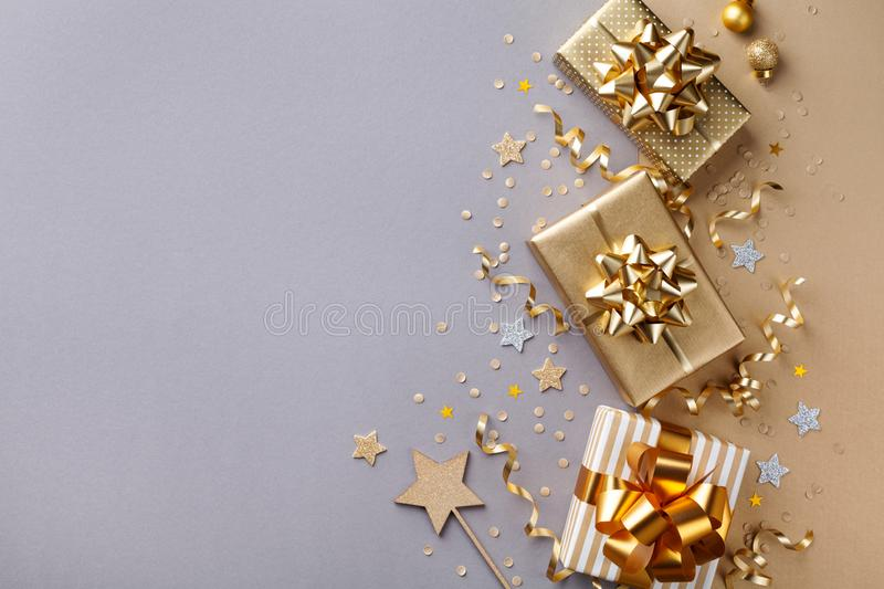 Golden gift or present boxes with golden bows and star confetti on bicolor background top view. Flat lay composition for Christmas. Card stock image