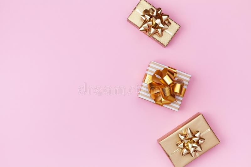 Golden gift or present boxes on pink background top view. Festive composition for birthday, christmas or wedding. Flat lay. Style stock image