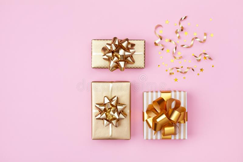 Golden gift or present boxes and star confetti on pink background top view. Flat lay for birthday, christmas or wedding. Golden gift or present boxes and star stock photography