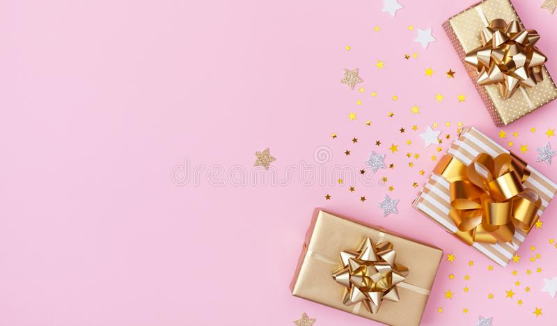Golden gift or present boxes and star confetti on pink background top view. Flat lay for birthday, christmas or wedding. Golden gift or present boxes and star stock image