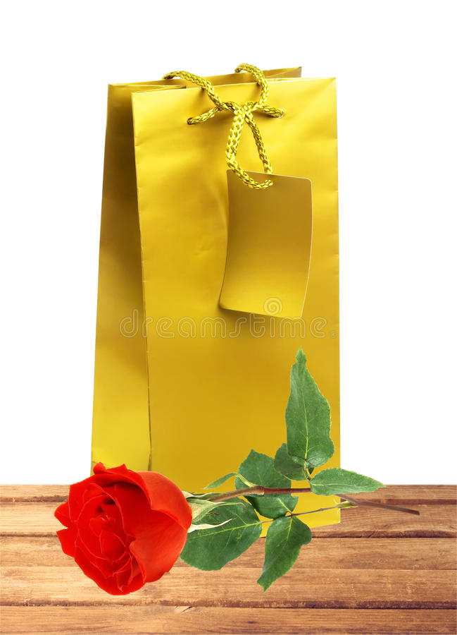 Golden gift shopping bag and red rose isolated on white. Background stock photo