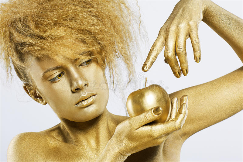 Golden girl with apple. Portrait of girl with golden bodyart posing with golden apple in her hands on gray