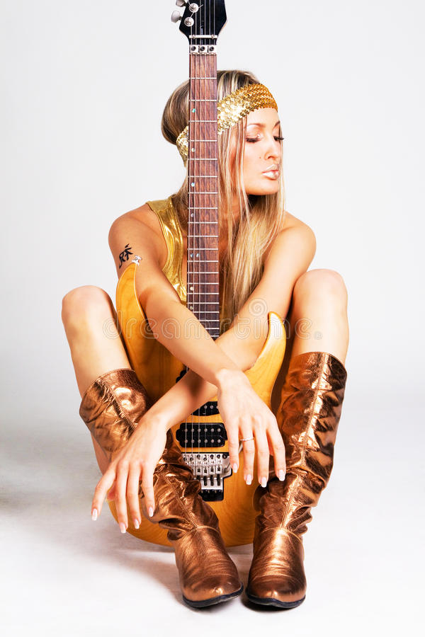 Golden girl with electric guitar royalty free stock image