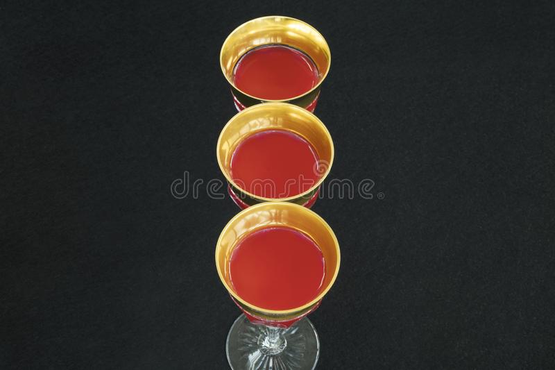 Golden glasses filled with a red liquid in black background.  royalty free stock image