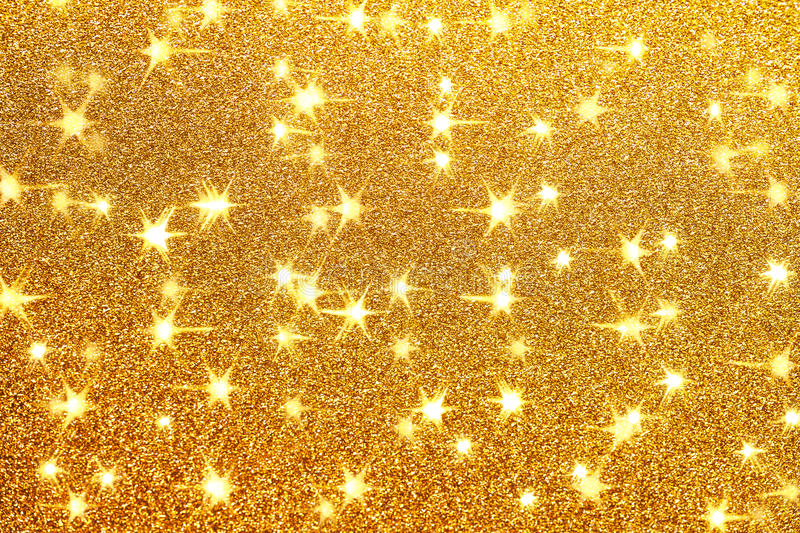 Golden glitter background with little sparkles. And shining stars. Festive backdrop fot your text or design royalty free stock photo