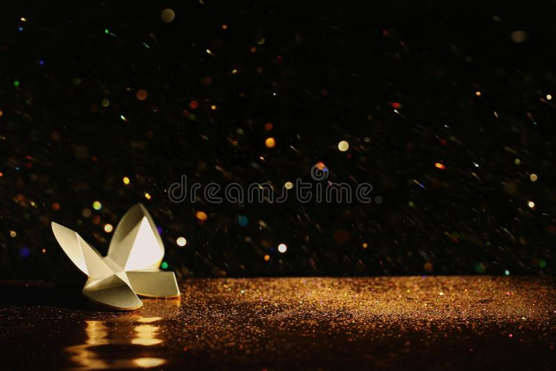 Golden glitter and decorative butterfly against black. Space for text stock photos