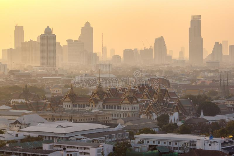 Golden grand palace of bangkok with skyscraper view of cityscape at sunrise time stock photography