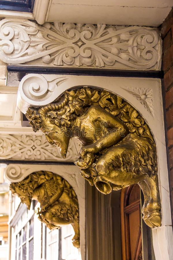 Golden grotesque stone golden satyrfaun, architectural detail of the medieval building. Golden grotesque stone golden satyr faun, architectural detail of the stock images