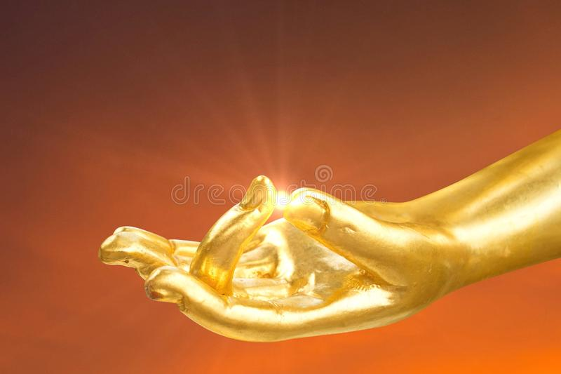 Golden hand of buddha statue with lens flare at finger stock photos