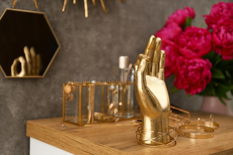 Golden hand  holder, jewelry and accessories on dressing table near grey wall. Space for text. Golden hand shaped holder, jewelry and accessories on dressing stock image