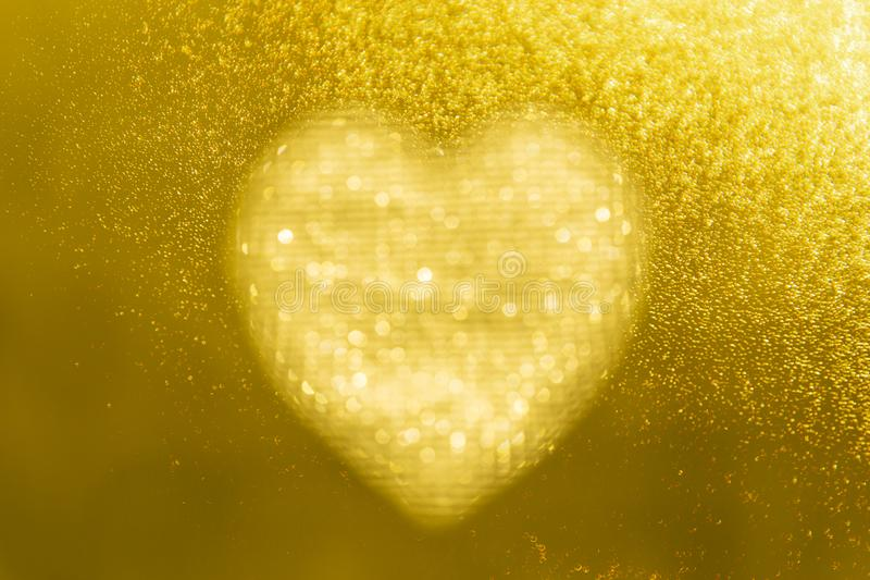 Golden heart bokeh frame on a gold background with space for your valentine wording concept stock images
