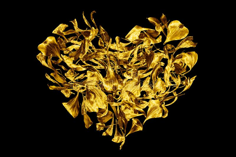 Golden heart made of flower petals on black background isolated closeup, decorative gold heart shape ornament, art floral pattern. Yellow metallic shiny design royalty free stock photos