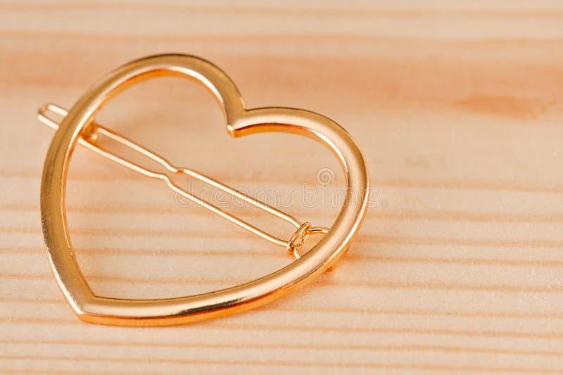 Golden heart shaped hair clip closeup shot on a wooden surface stock photos