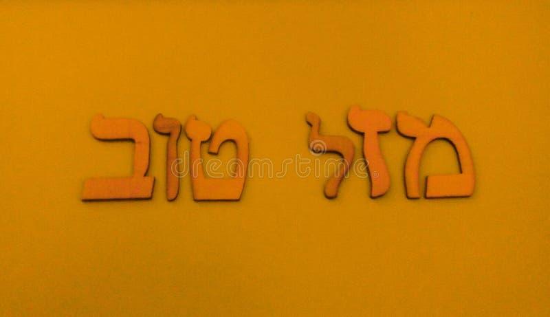 "Hebrew words. Golden Hebrew expression on golden backround.In Hebrew""Mazal Tov"" and in English""Good Luck"" stock illustration"