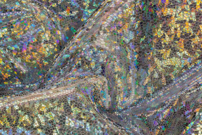 Golden holographic fabric with folds. Abstract geometric background or texture stock images