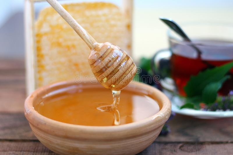 Golden honey in a clay bowl with fragrant tea and honeycombs royalty free stock photography