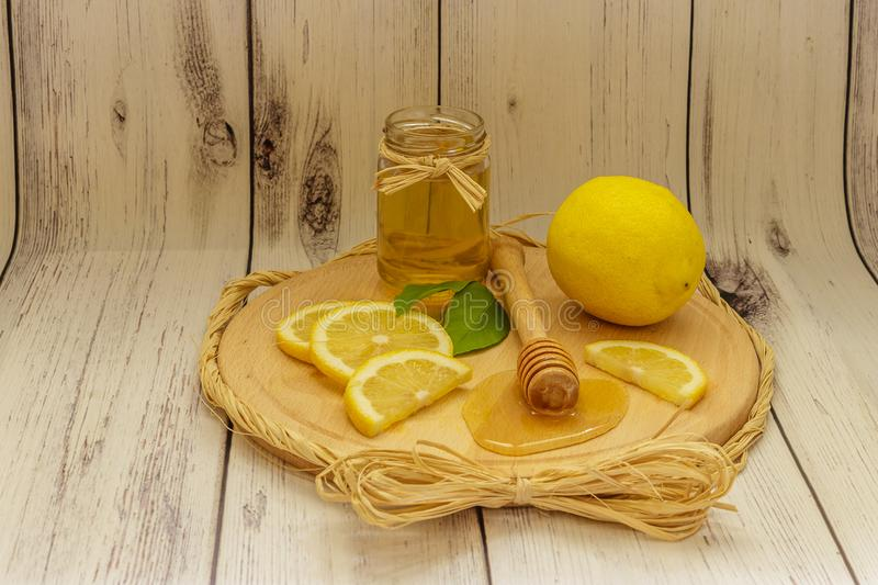 Golden honey in a jar, lemon slices and lemon leaves on a wooden royalty free stock photo
