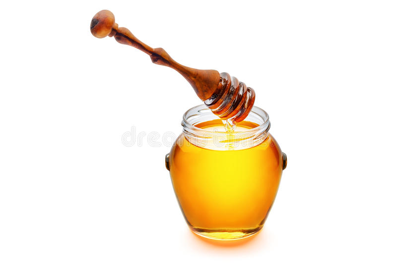 Golden honey in a jar with a wooden honey dripper pouring honey.  stock images