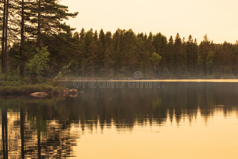Golden hour beautiful reflection of island in misty lake. Beautiful reflection of a small island with trees in water. Golden hour a calm summer evening, with stock image