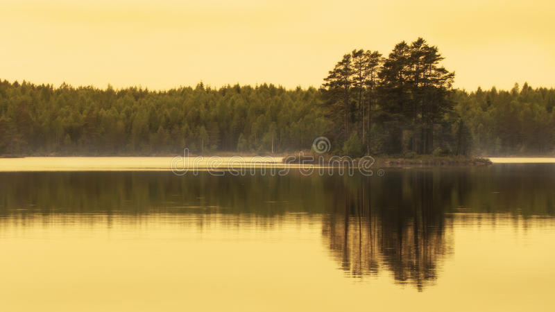 Golden hour beautiful reflection of small island in lake. Beautiful reflection of a small island with trees in water. Golden hour a calm summer evening stock photography