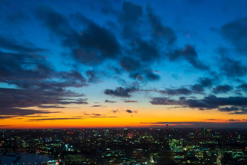 Golden hour - dark blue clouds with an orange light sky background and city light midnight evening time royalty free stock photo