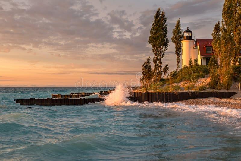Golden Hour at Point Betsie Lighthouse on Lake Michigan. Waves crash along the Lake Michigan shore in front of Point Betsie Lighthouse, during sunset royalty free stock image