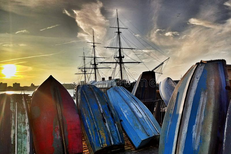 Golden hour in Portsmouth. This is the golden hour in Portsmouth, UK. HMS Warrior beside of the boats stock images