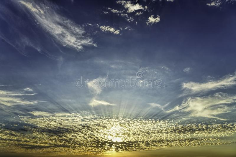 Golden hour sun rays through the beautiful low white scattered clouds on orange blue sky royalty free stock images