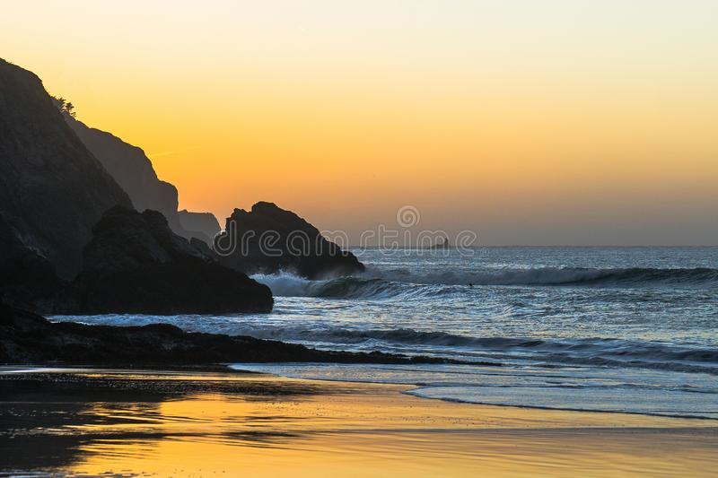 Golden Hour Sunset in Rarely Accessible Cove. Beautiful golden sunset hidden beneath the golden gate bridge in San Francisco, CA. Only accessible at the lowest royalty free stock image