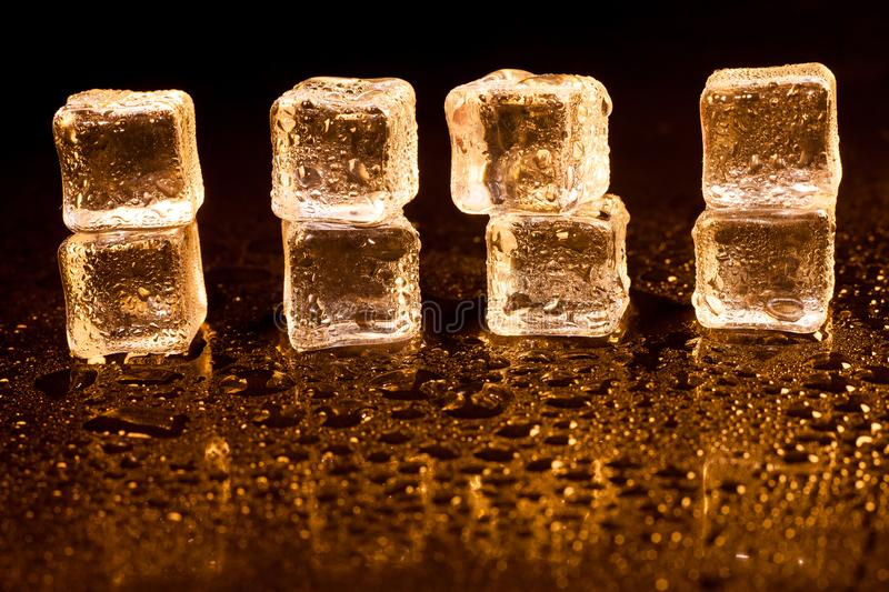 Golden ice cubes on black background. Alcohol, alcoholic, amber, bar, beverage, bottle, bourbon, brandy, brown, close-up, closeup, cocktail, cognac, cold, cool stock image