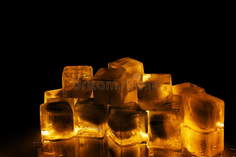 Golden ice cubes on black background isolated close up, transparent frozen amber color water with yellow back light and reflection royalty free stock images